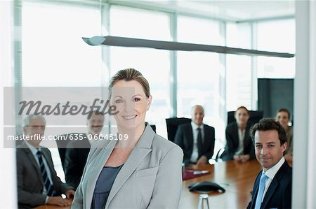 Portrait of smiling businesswoman and co-workers in conference room Stock Photo - Premium Royalty-Free, Image code: 635-06045109