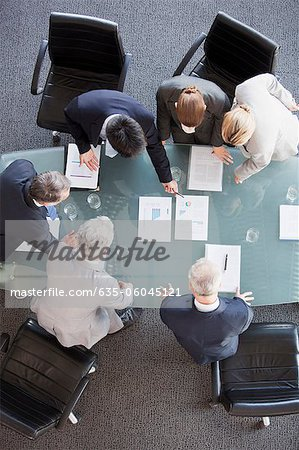 Business people huddled around paperwork on table Stock Photo - Premium Royalty-Free, Image code: 635-06045121