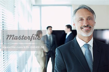 Portrait of smiling businessman with co-workers in background Stock Photo - Premium Royalty-Free, Image code: 635-06045124