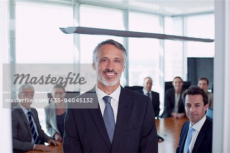 Portrait of smiling businessman and co-workers in conference room Stock Photo - Premium Royalty-Free, Image code: 635-06045132