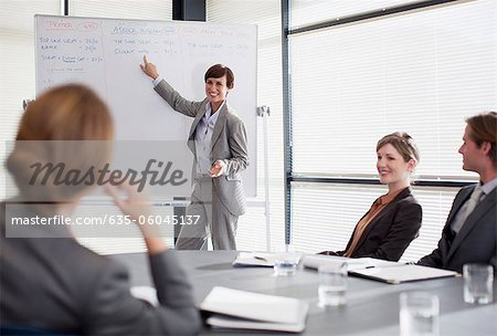 Businesswoman at whiteboard presenting to co-workers Stock Photo - Premium Royalty-Free, Image code: 635-06045137