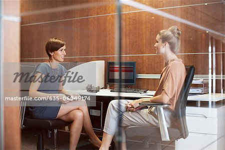 Businesswomen talking in office Stock Photo - Premium Royalty-Free, Image code: 635-06045174