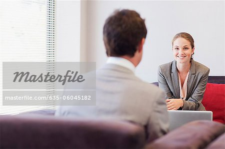 Business people talking face to face in lobby Stock Photo - Premium Royalty-Free, Image code: 635-06045182