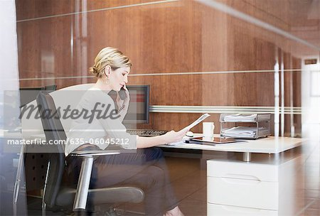 Businesswoman talking on telephone at desk in office Stock Photo - Premium Royalty-Free, Image code: 635-06045212