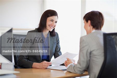 Businesswomen with paperwork talking face to face Stock Photo - Premium Royalty-Free, Image code: 635-06045215