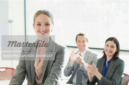 Co-workers clapping for smiling businesswoman Stock Photo - Premium Royalty-Free, Image code: 635-06045227