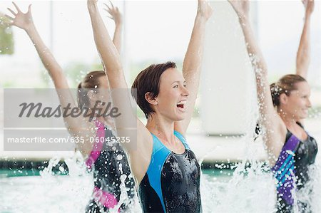 Enthusiastic women jumping in swimming pool