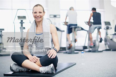Portrait of smiling woman sitting on exercise mat in gymnasium Stock Photo - Premium Royalty-Free, Image code: 635-06045239