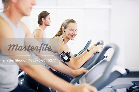 Portrait of smiling woman on exercise bike in gymnasium Stock Photo - Premium Royalty-Free, Image code: 635-06045277