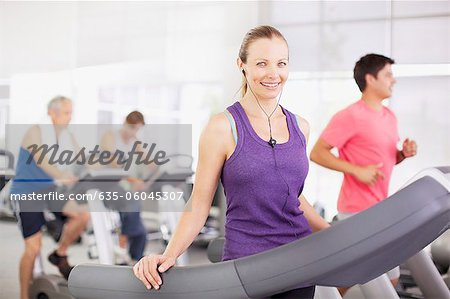 Portrait of smiling woman on treadmill in gymnasium Stock Photo - Premium Royalty-Free, Image code: 635-06045307