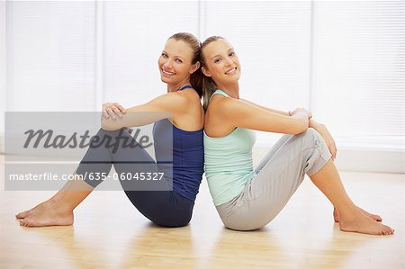 Portrait of smiling women sitting back to back in fitness studio Stock Photo - Premium Royalty-Free, Image code: 635-06045327