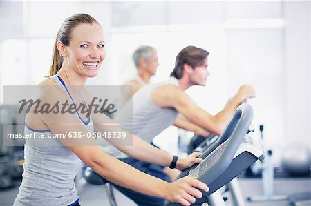 Portrait of smiling woman on exercise machine in gymnasium Stock Photo - Premium Royalty-Free, Image code: 635-06045339