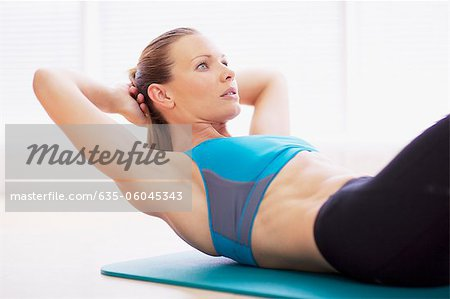 Serious woman in sports bra doing sit-ups on exercise mat