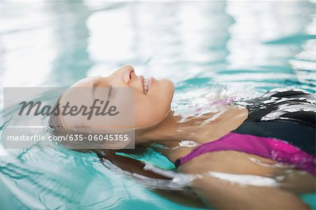 Close up of smiling woman floating on back in swimming pool Stock Photo - Premium Royalty-Free, Image code: 635-06045355
