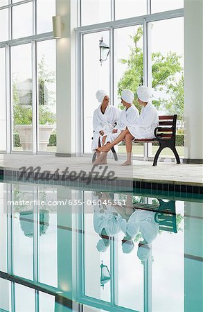 Women in bathrobes talking on bench poolside at spa Stock Photo - Premium Royalty-Free, Image code: 635-06045361