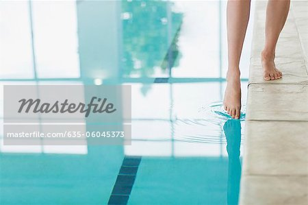 Woman dipping toe in swimming pool Stock Photo - Premium Royalty-Free, Image code: 635-06045373