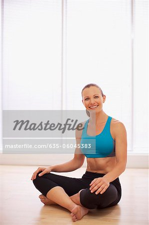 Portrait of smiling woman wearing sports bra in fitness studio Stock Photo - Premium Royalty-Free, Image code: 635-06045383