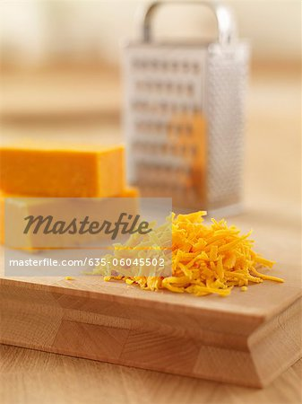 Close up of shredded cheese on cutting board Stock Photo - Premium Royalty-Free, Image code: 635-06045502