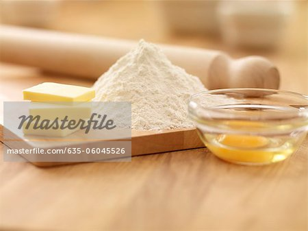 Rolling pin, flour, butter and egg on cutting board Stock Photo - Premium Royalty-Free, Image code: 635-06045526