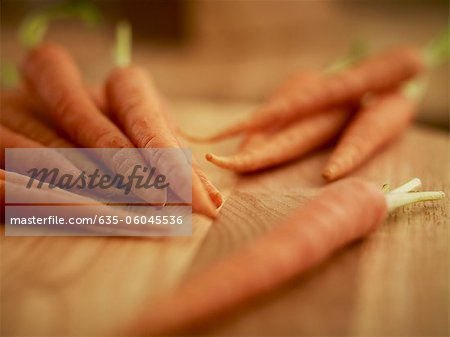 Close up of carrots on cutting board Stock Photo - Premium Royalty-Free, Image code: 635-06045536