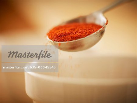 Close up of spice in measuring spoon sprinkling into bowl Stock Photo - Premium Royalty-Free, Image code: 635-06045545