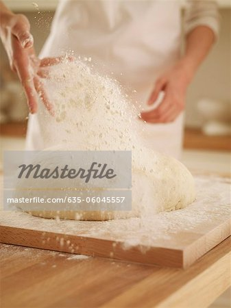 Woman dusting dough with flour Stock Photo - Premium Royalty-Free, Image code: 635-06045557