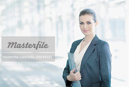 Portrait of smiling woman standing in corridor Stock Photo - Premium Royalty-Free, Image code: 635-06045591