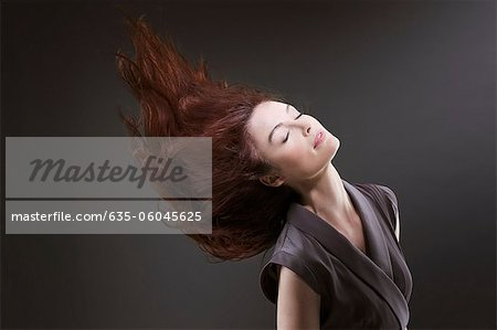 Woman with eyes closed flipping hair Stock Photo - Premium Royalty-Free, Image code: 635-06045625