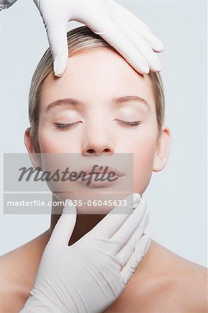 Close up of rubber-gloved hands touching woman's face Stock Photo - Premium Royalty-Free, Image code: 635-06045633