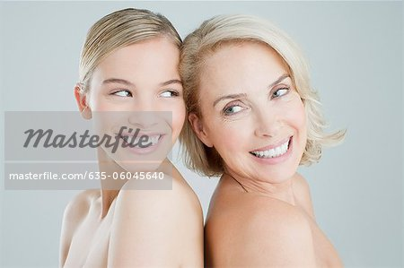 Smiling mother and daughter back to back Stock Photo - Premium Royalty-Free, Image code: 635-06045640