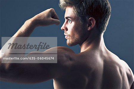 Rear view portrait of man flexing biceps muscles Stock Photo - Premium Royalty-Free, Image code: 635-06045674