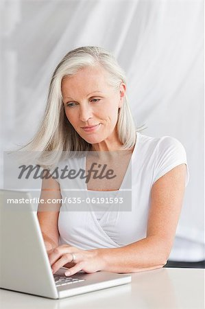 Woman typing on laptop Stock Photo - Premium Royalty-Free, Image code: 635-06191593