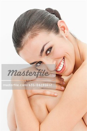 Close up portrait of smiling nude woman hugging knees