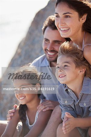 Smiling family hugging on beach Stock Photo - Premium Royalty-Free, Image code: 635-06191619