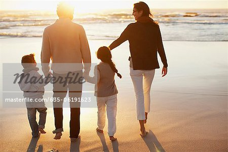 Family holding hands and walking on beach at sunset Stock Photo - Premium Royalty-Free, Image code: 635-06191623