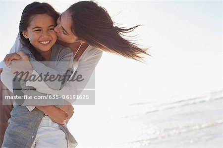Mother hugging and kissing daughter on beach Stock Photo - Premium Royalty-Free, Image code: 635-06191625