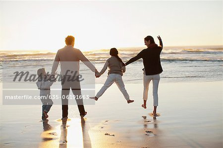 Family holding hands on beach at sunset Stock Photo - Premium Royalty-Free, Image code: 635-06191663