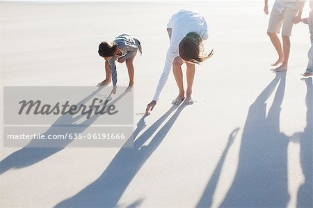 Family writing in sand on beach Stock Photo - Premium Royalty-Free, Image code: 635-06191666