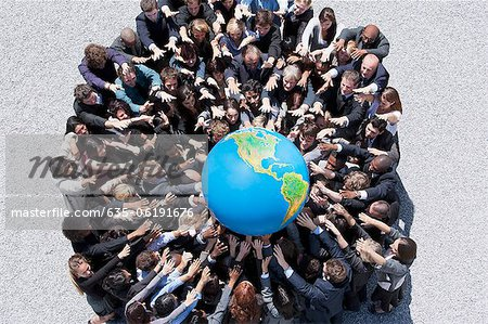 Crowd of business people in huddle reaching for globe Stock Photo - Premium Royalty-Free, Image code: 635-06191676