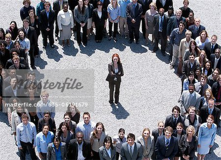 Portrait of businesswoman standing at center of circle formed by business people Stock Photo - Premium Royalty-Free, Image code: 635-06191679