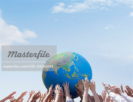 Crowd reaching for globe Stock Photo - Premium Royalty-Free, Image code: 635-06191683