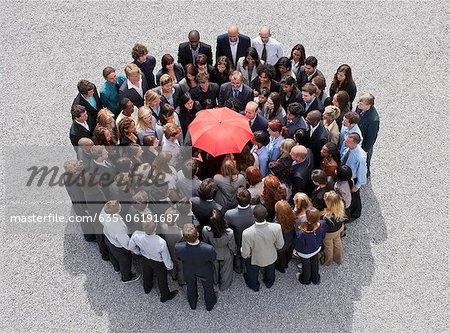 Umbrella at center of circle formed by business people Stock Photo - Premium Royalty-Free, Image code: 635-06191687
