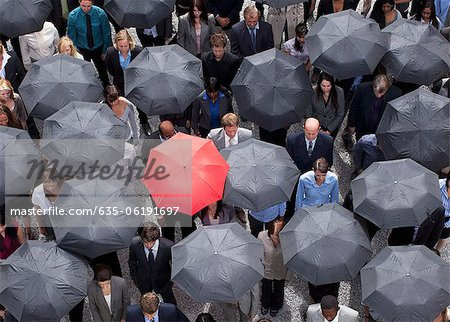 Red umbrella standing out in crowd of business people Stock Photo - Premium Royalty-Free, Image code: 635-06191697