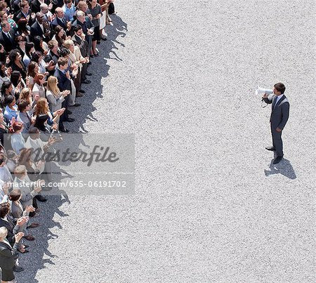 Businessman with bullhorn talking to crowd of people Stock Photo - Premium Royalty-Free, Image code: 635-06191702