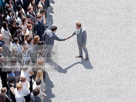 Businessman shaking man's hand in crowd Stock Photo - Premium Royalty-Free, Image code: 635-06191706