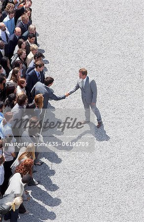 Businessman shaking man's hand in crowd Stock Photo - Premium Royalty-Free, Image code: 635-06191709