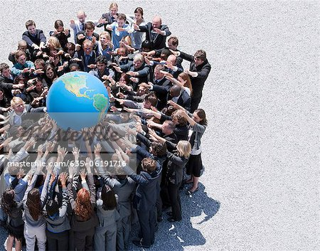 Crowd of business people in huddle reaching for globe Stock Photo - Premium Royalty-Free, Image code: 635-06191716