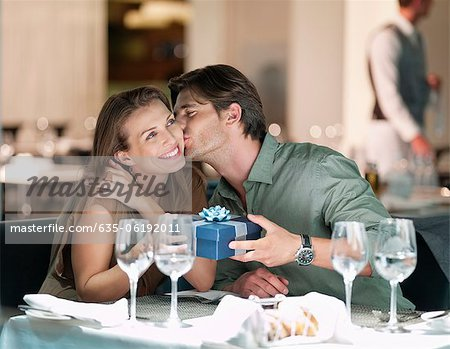 Man kissing and giving gift to woman in restaurant Stock Photo - Premium Royalty-Free, Image code: 635-06192011