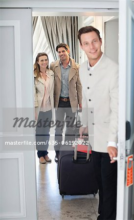 Portrait of bellman opening hotel room door with couple in background Stock Photo - Premium Royalty-Free, Image code: 635-06192022