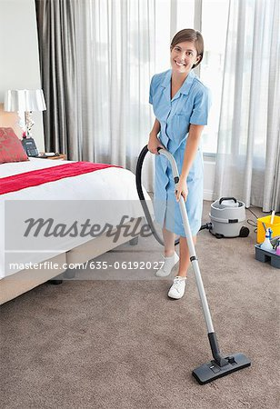 Portrait of smiling maid vacuuming hotel room Stock Photo - Premium Royalty-Free, Image code: 635-06192027